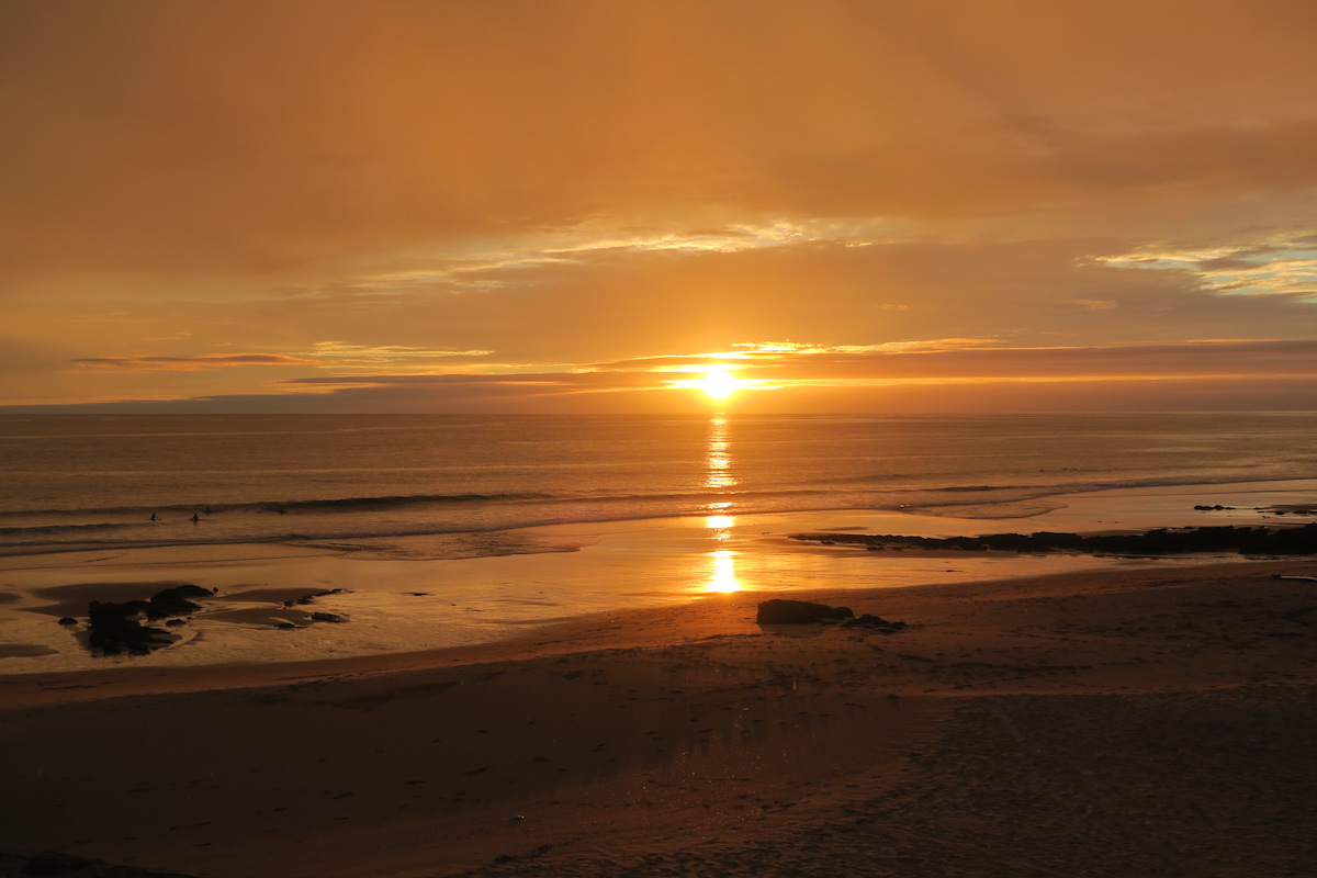 This is a beautiful photo of the sun setting in Sintra, at Praia das Macas.