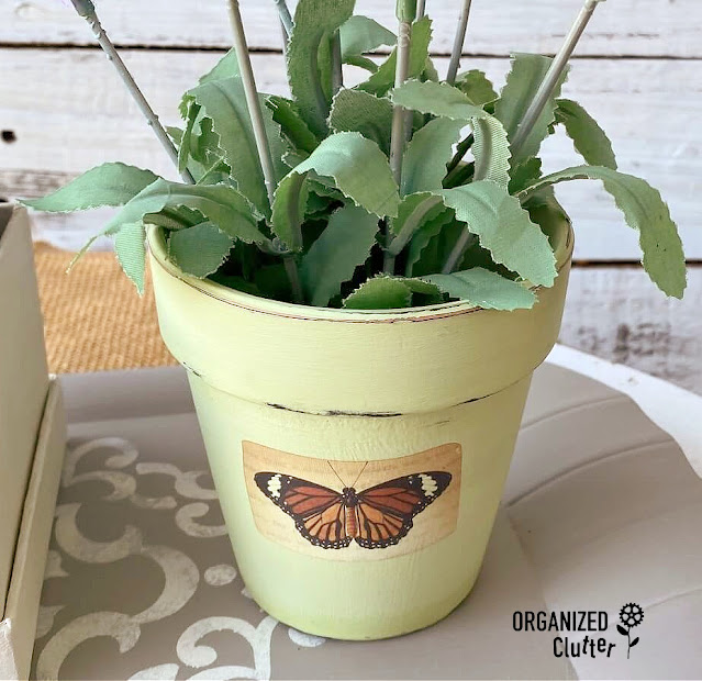 Photo of painted pot with rub on butterfly transfer.
