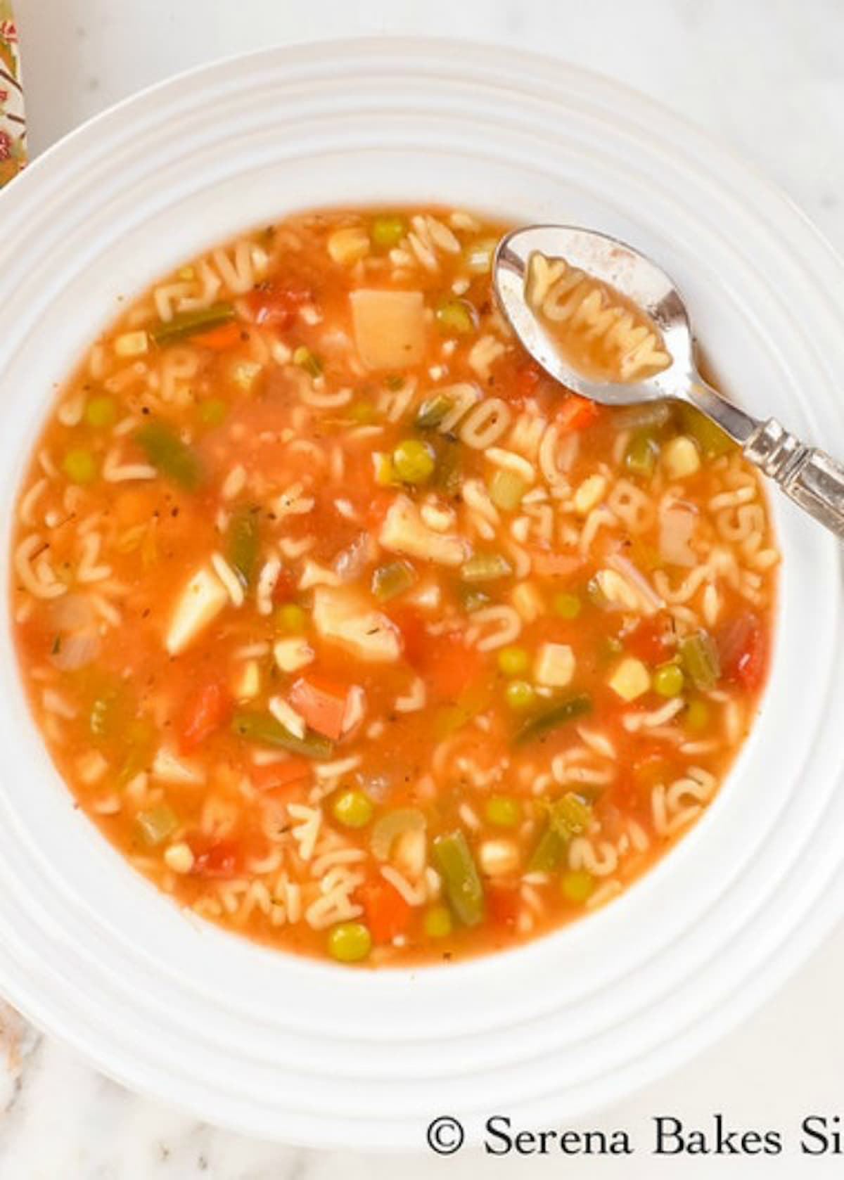 Homemade Alphabet Vegetable Soup filled with alphabet pasta, diced potatoes, green beans, peas, and corn in a white soup bowl with a spoon resting on the edge with the word yummy spelled with alphabet noodles in the spoon.