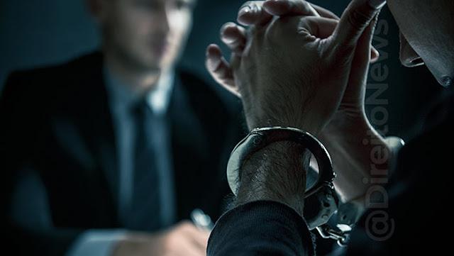 Homem com as mãos algemadas sentado em frente a outro homem com roupas sociais.