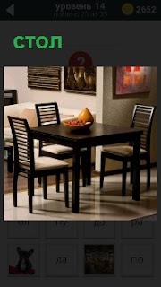 На кухне стоит стол и три стула. на поверхности стола блюдо с фруктами, а на стенах висят картины
