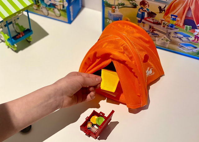 The pop up PLAYMOBIL family tent, a sleeping bag and a suitcase with plates and food in
