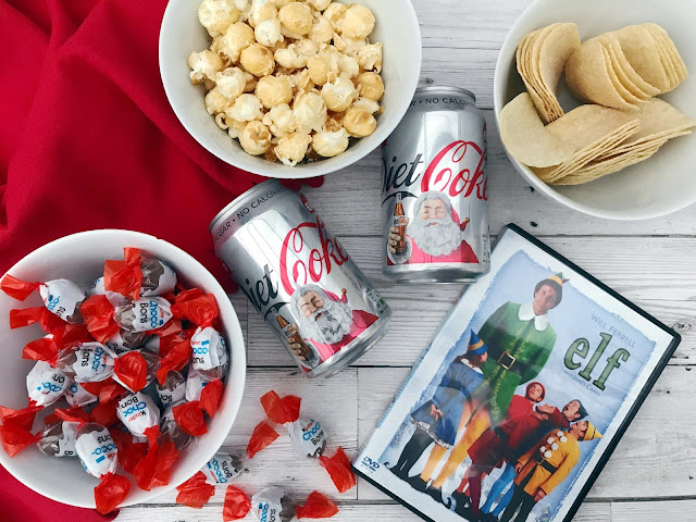 Flat lay showing a red blanket, bowl of popcorn, crisps, kinder chocolates, cans of diet coke with Santa on and boxed Elf dvd