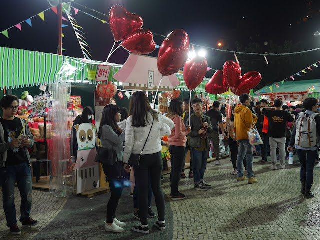 people selling red heart-shaped balloons