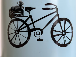 A Moose In The Basket Of A Bicycle