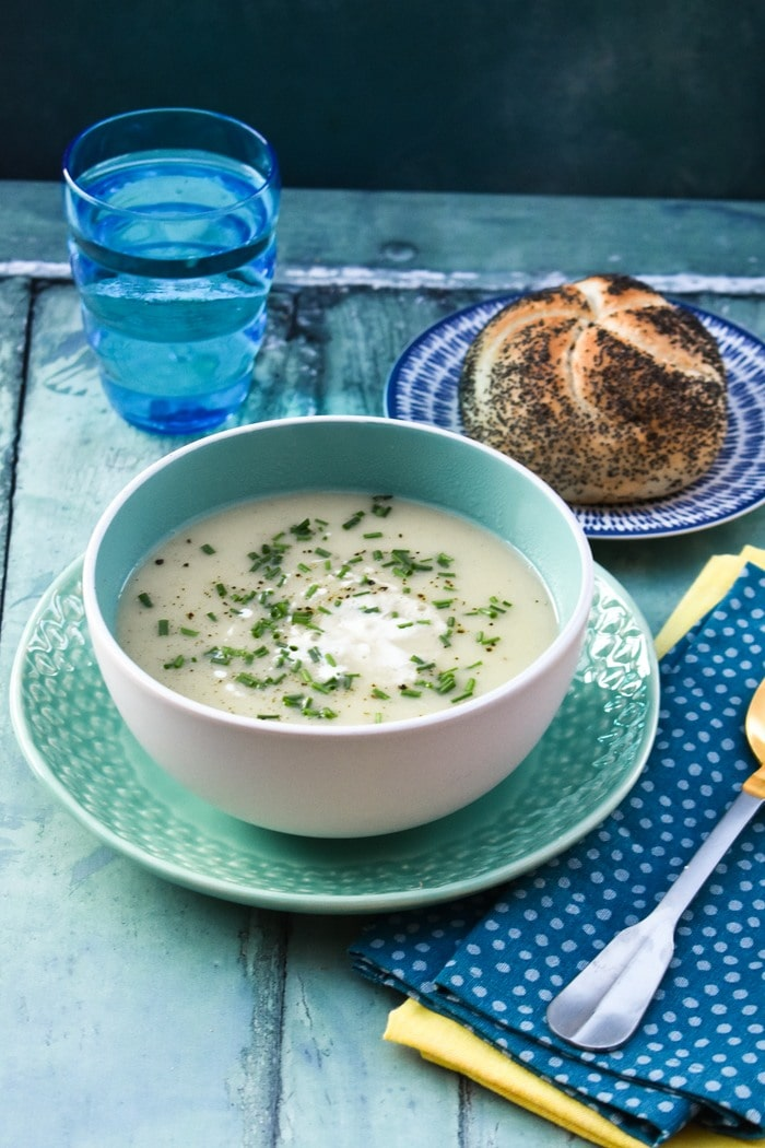 Creamy Cauliflower Soup in a bowl served with seeded brown roll