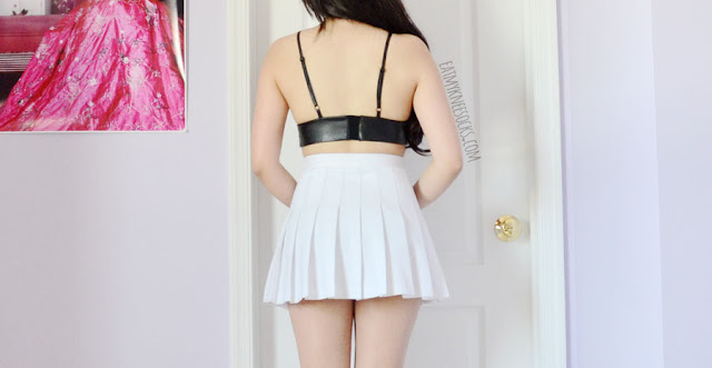 Details on the faux leather lace top crop top triangle bralette from Dresslink, paired with a white pleated American Apparel tennis skirt.