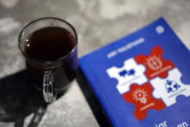 Membaca buku sambil menyesap kopi