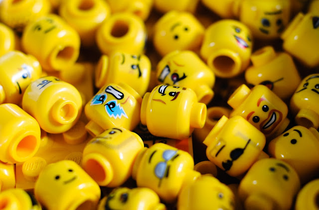 Pile of Lego mini figure heads, all with different expressions
