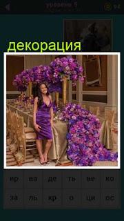 девушка в помещении около стола показывает свою декорацию к торжеству
