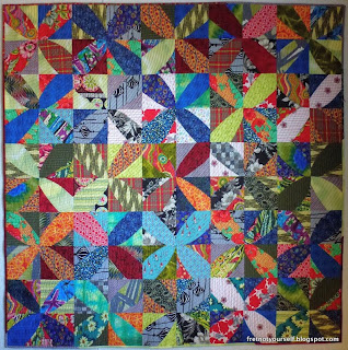 Brightly colored fabrics in red, orange, blue, chartreuse, black and white spin across the quilt in windmill pattern.