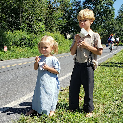 Two Amish children cheering on riders.