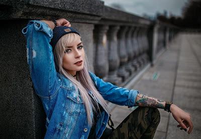 Linda chica rubia con chaqueta vaquera azul y gorro sentada en la calle