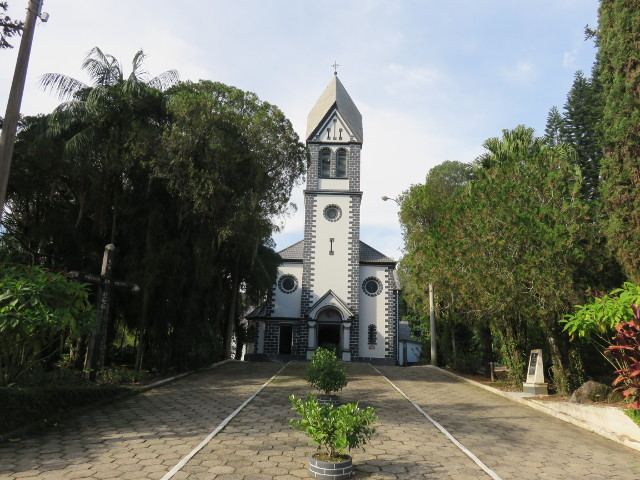 A white and gray church surrounded by green trees.