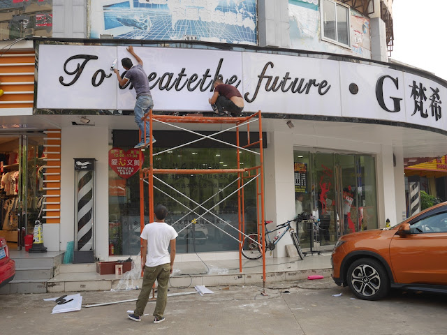 "young men repairing a storefront sign with the words ""To create the future"""