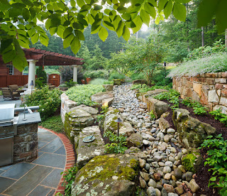 Backyard patio alongside raised terraces and rock channels (aka swales and berms