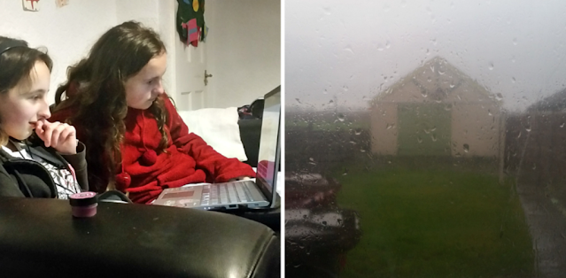 My girls looking at the laptop and a rainy window