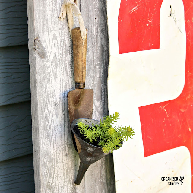 Photo of a succulent planter created from a garden spade & funnel.