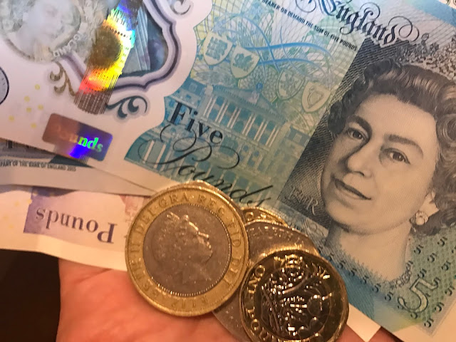 A hand holding notes and loose change, british pounds to illustrate how money can be saved in school holidays