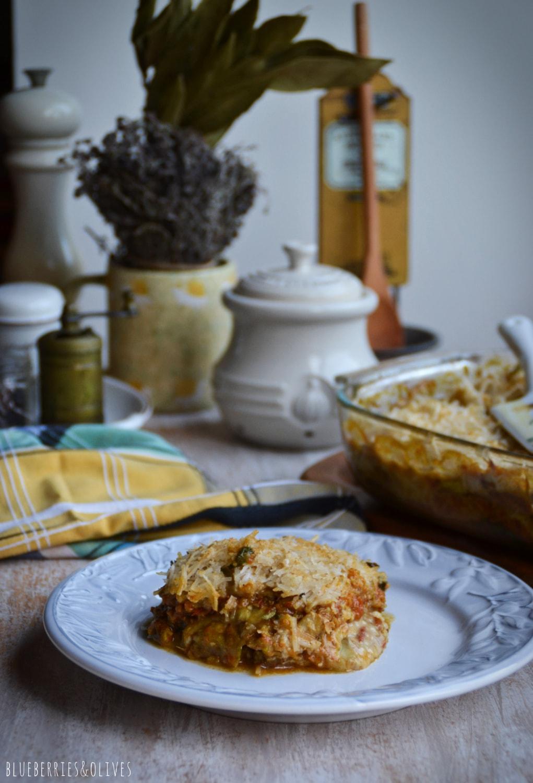 Lasaña de berenjenas en fuente de cristal sobre tabla de madera, con ingredientes de fondo, hierbas aromáticas, laurel seco, molinillo pimienta