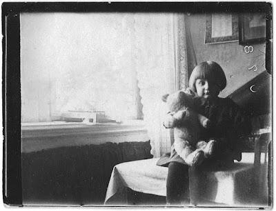 Vierjährige mit Teddy sitzt auf dem Esstisch