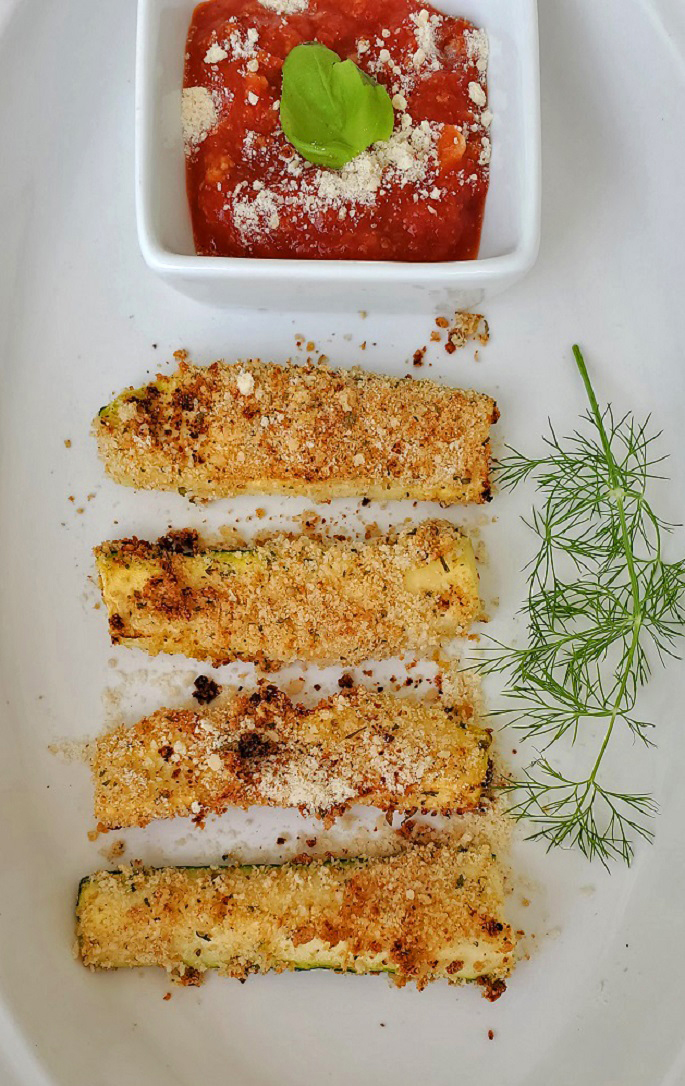 this bread zucchini air fried on a white plate with dill, ,marinara sauce and pecorino romano cheese