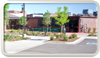 "The front of the Colorado Center for the Blind, showing the new landscaping and patio with picnic tables, with iris, lilacs and other flowers in bloom.  The sign on the side of the building with ""Colorado Center for the Blind"" and ""National Federation of the Blind"" is visible"