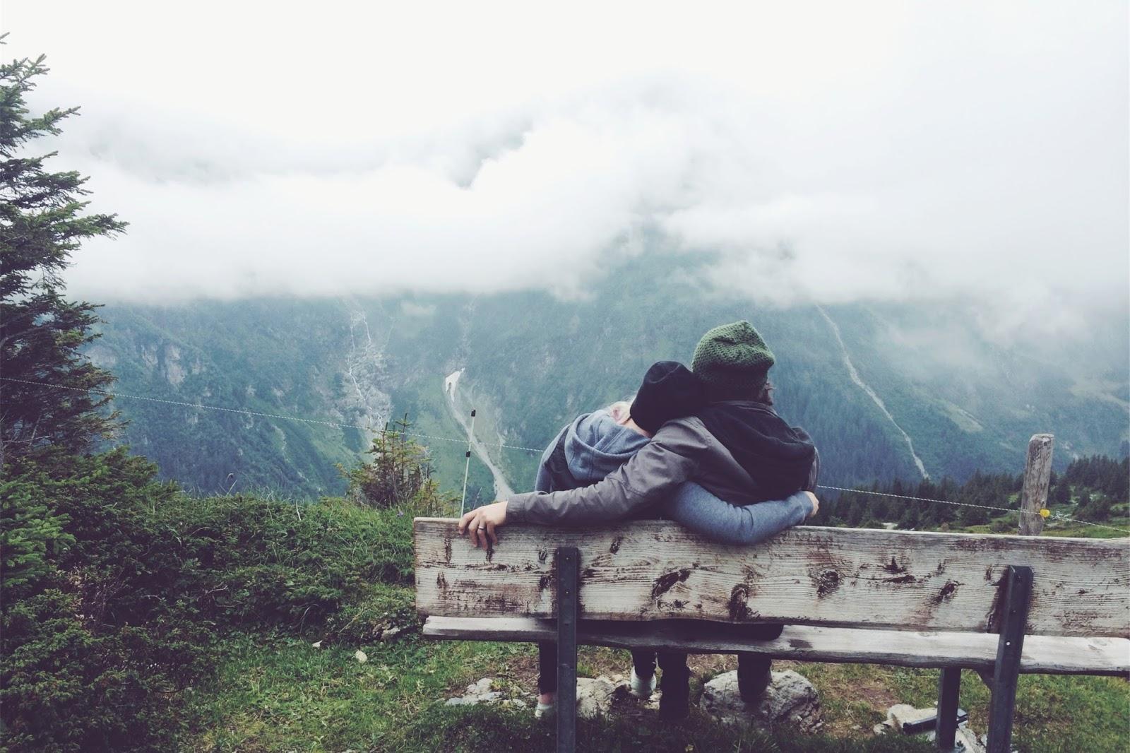 casal sentado costas frio olhando paisagem