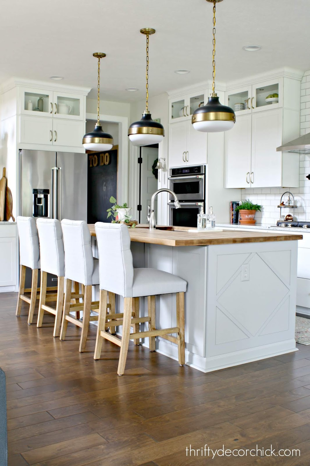 white kitchen with gray island black and brass fixtures