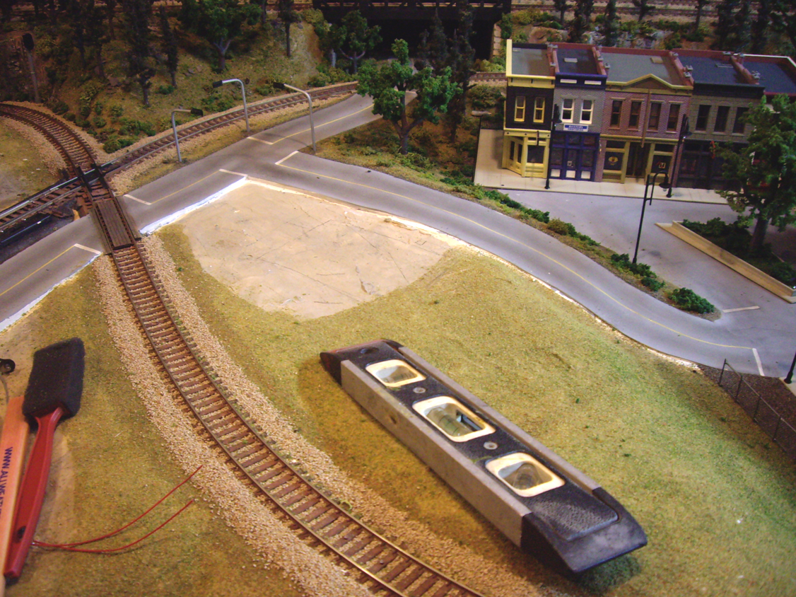 An unfinished space of plaster hard shell terrain beside completed railroad track