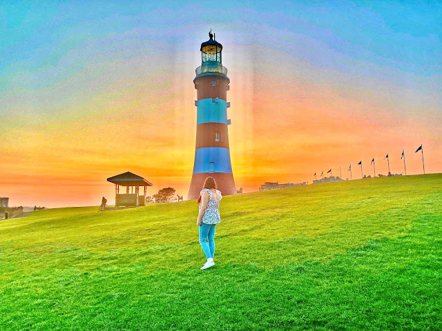 Plymouth Hoe at sunset with a girl posing in front of the lighthouse