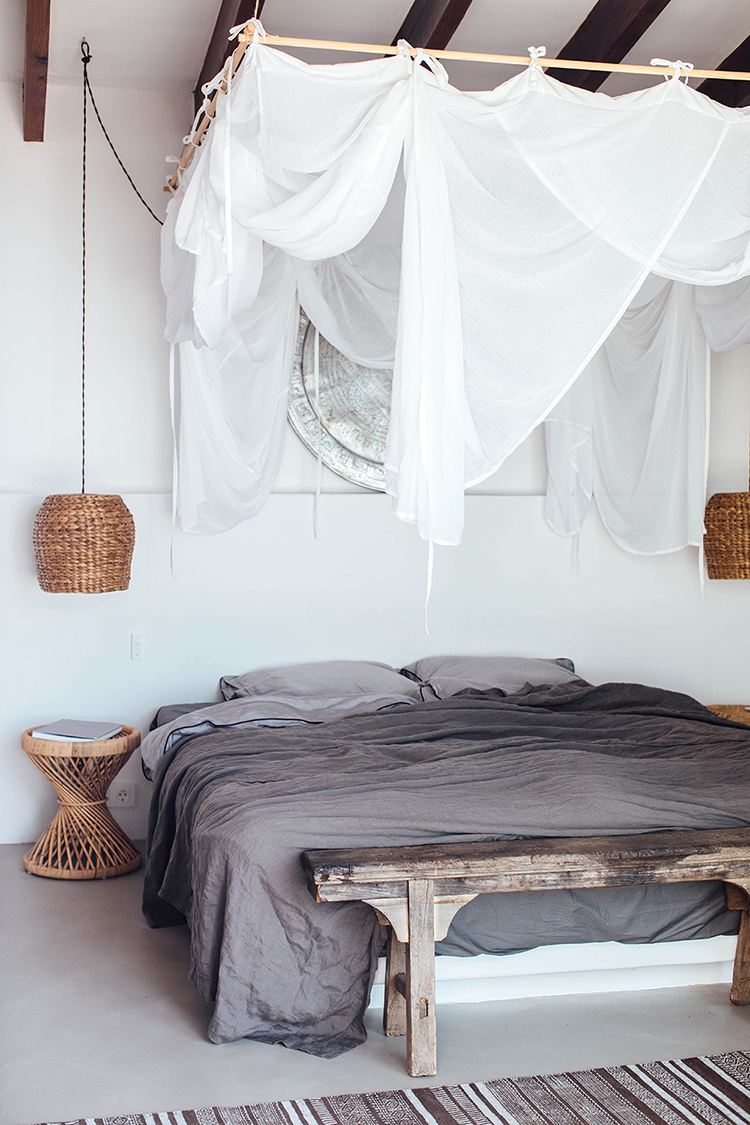 Modern rustic bedroom with bed drapes, linen bedding, vintage furniture and woven pendant lamp. Villa Son Font via Our Food Stories