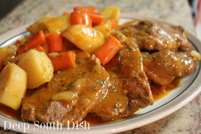 Russet potatoes and chunks of carrots and onion are cooked stovetop in a tomato-based sauce with seasoned pork chops or pork steaks, for an easy one pot meal.