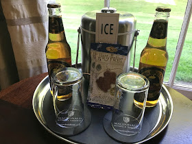 two glass bottle of butterbeer and two chocolate frogs on a table