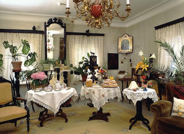 Kuva talon salista.Etualalla pöytiä juhlavasti koristeluna, taustalla korkea peili.