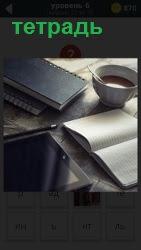 на столе лежат блокноты и тетрадь для записей, стоит чашка с кофе