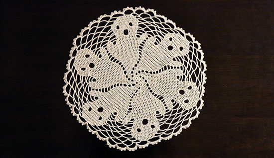 Top view of off-white crocheted cotton ghost-motif doily on a dark background.