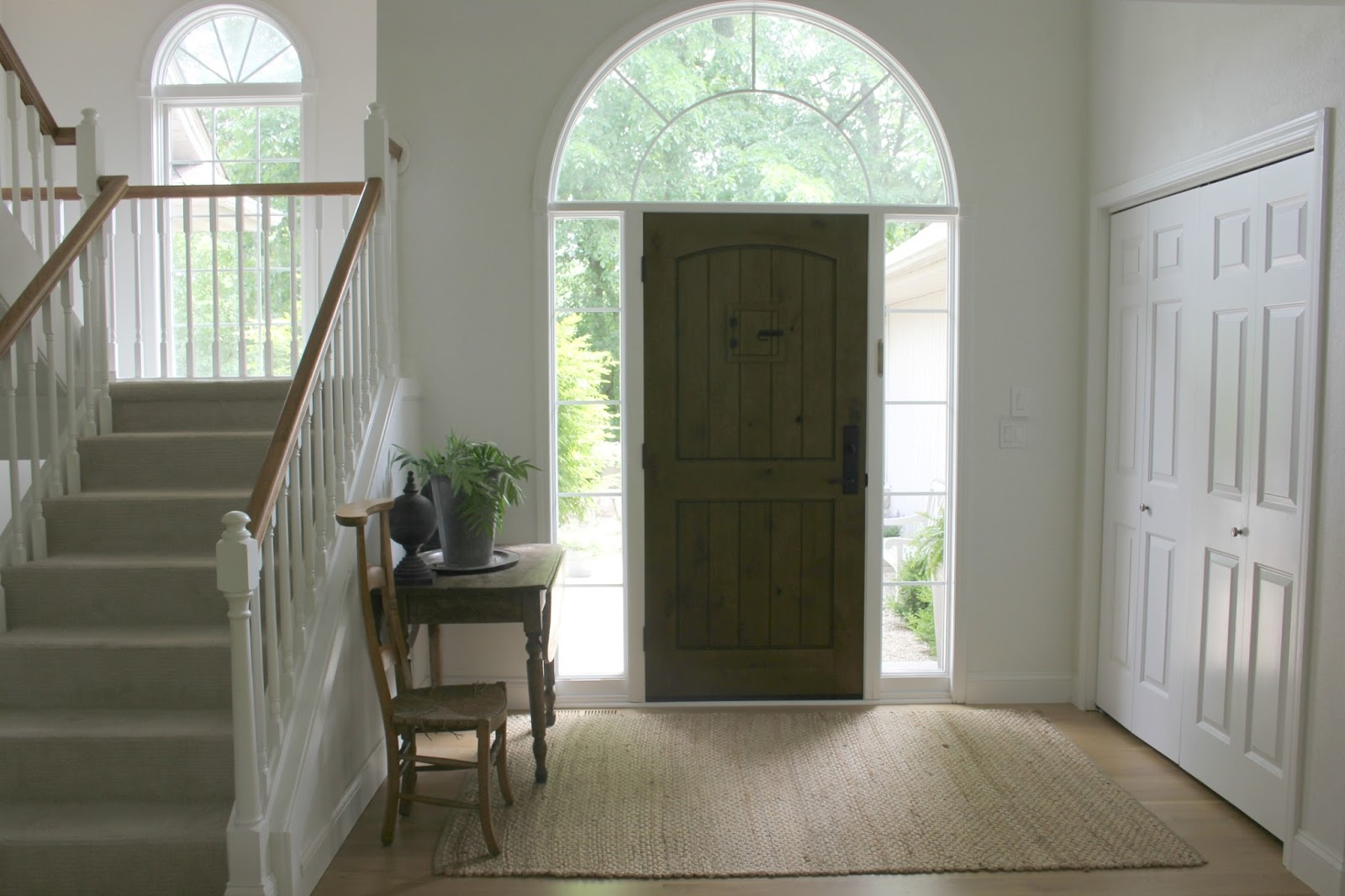 Front entry with knotty alder door, vintage table, and vintage French prayer chair - Hello Lovely Studio