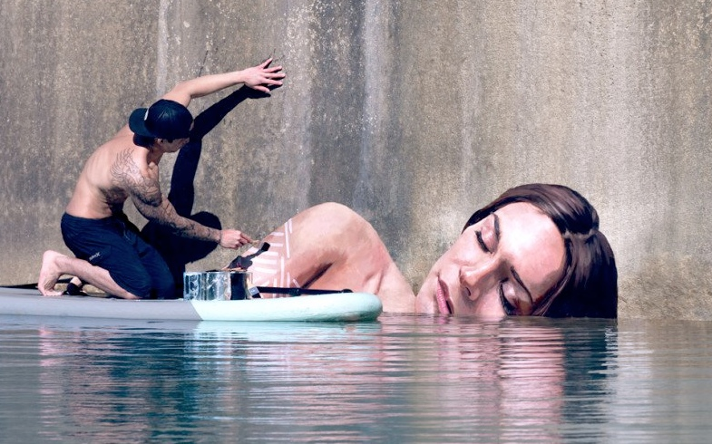 Artist Paints Murals of Women While Floating on a Surfboard