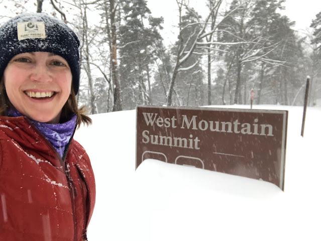 woman standing in snow by mountain road sign