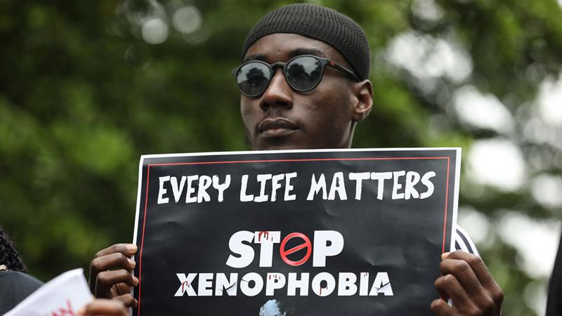 A demonstrator holds a sign during a protest against xenophobia in Abuja, Nigeria
