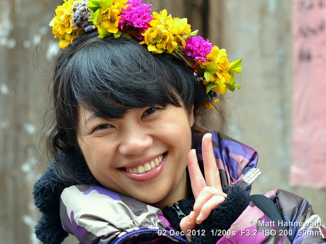people, street portrait, East Asia, China, V sign, Chinese beauty, floral hair wreath, Chinese woman, © Matt Hahnewald, Facing the World, 50 mm prime lens, Xingping, Guangxi Province