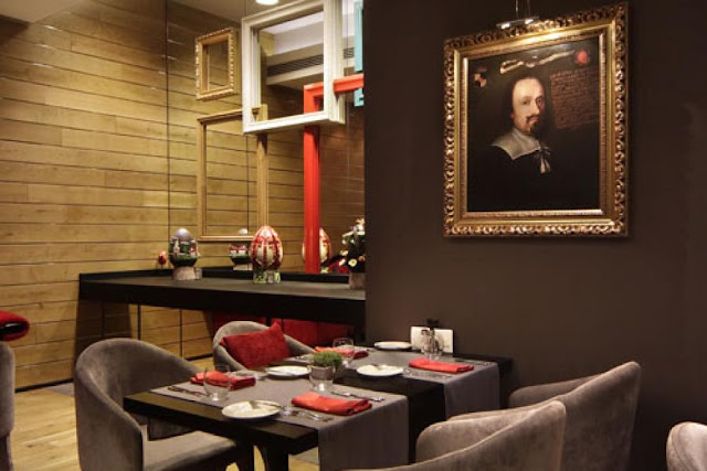 Picture of black square dining table by the wall with William Shakespeare picture on it