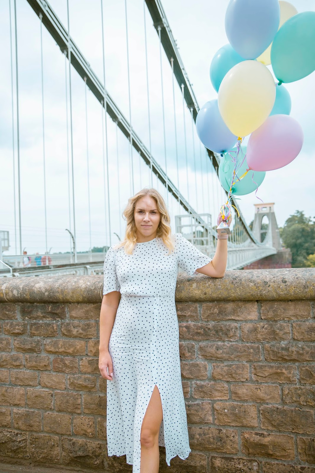 Rachel Emily holding pastel coloured balloons in a white dress by the Clifton Suspension Bridge, Bristol