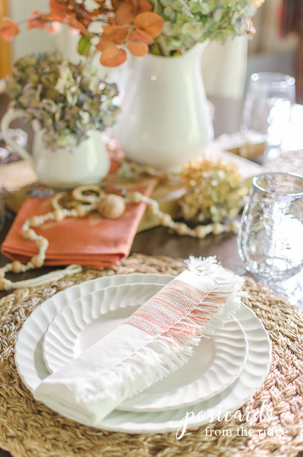 fall table setting with fringed cloth napkin and white stoneware dishes