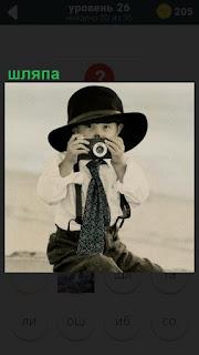 мальчик фотограф в шляпе фотографирует фотоаппаратом