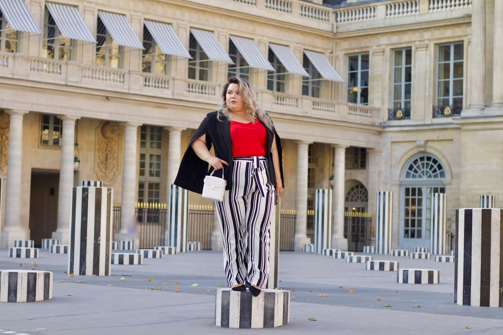 Chicago Plus Size Petite Fashion Blogger, influencer, YouTuber, and model Natalie Craig, of Natalie in the City, reviews Marée Pour Toi's Black and White Striped Pants, Red Washed Silk Charmeuse Tank, and Open Sleeve Blazer while visiting Paris, France and Les Deux Plateaux (also known as the Colonnes de Buren or stripe pillars) in Palais Royal.