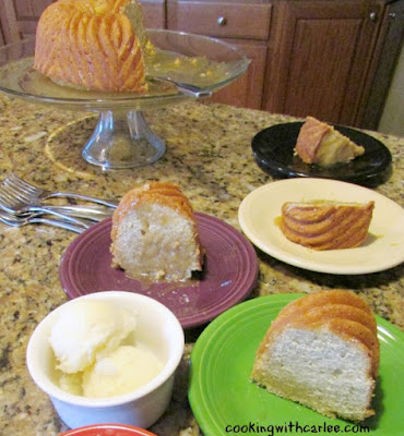slices of lemon bundt cake on various colored plates with remaining cake on pedastal stand in background