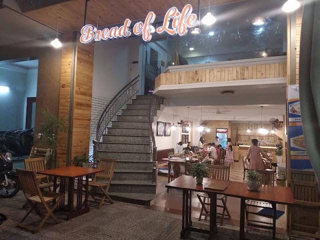 Entrada del restaurante Bread of Life en Vietnam con doble piso, unas escaleras que suben y gente al fondo comiendo en mesas