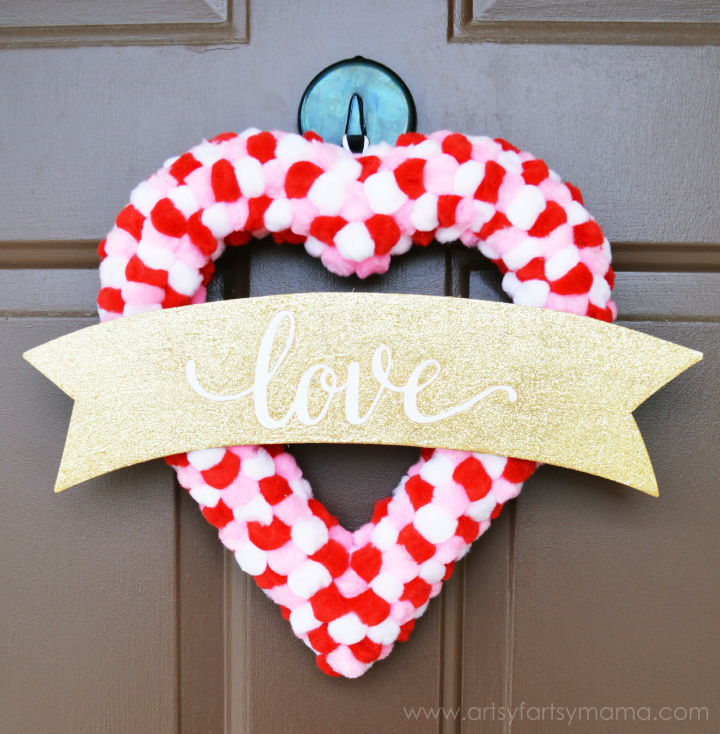 Easy Pom Pom Valentine Wreath Tutorial at artsyfartsymama.com #ValentinesDay